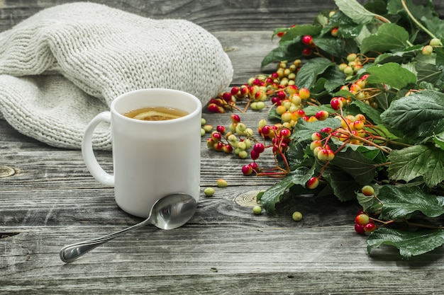 The cup of tea on a beautiful wooden background with winter sweater, berries, autumn Free Photo