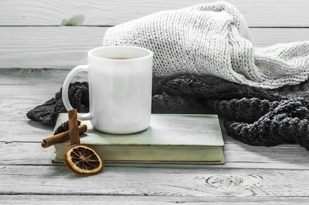 Cup of tea on a beautiful wooden wall with winter sweater, old book Free Photo