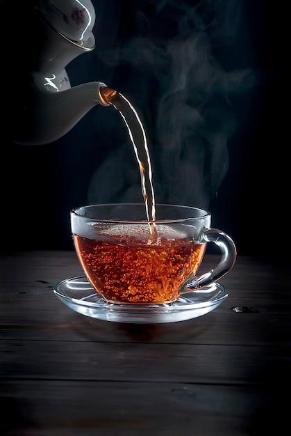 Premium Photo | Cup of tea on black background