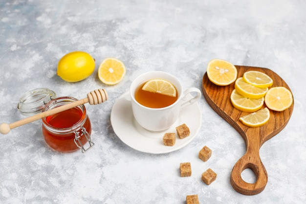 A cup of tea,brown sugar,honey and lemon on concrete  . top view, copy space Free Photo