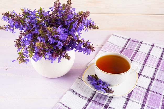 Cup of tea on checkered napkin and purple flowers Premium Photo