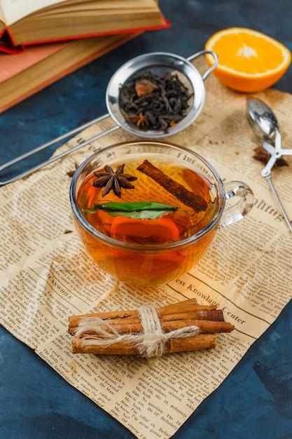 Tazza di tè, cannella e colini da tè con giornali, arancia e un libro sulla superficie in marmo blu Foto Gratuite