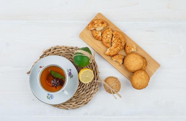 Tazza di tè e agrumi con i biscotti su un tagliere su una tovaglietta rotonda sulla superficie bianca Foto Gratuite