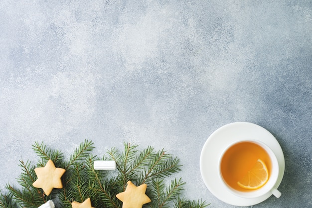 Cup of tea and cookies, pine branches, cinnamon sticks, anise stars Premium Photo