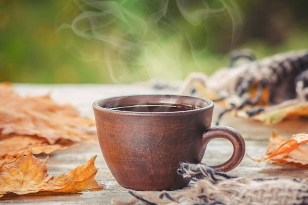 A cup of tea and a cozy autumn background. selective focus. Premium Photo