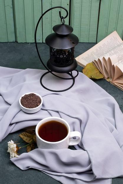 Una tazza di tè ed erbe in un piattino sul tavolo, un libro intorno Foto Gratuite