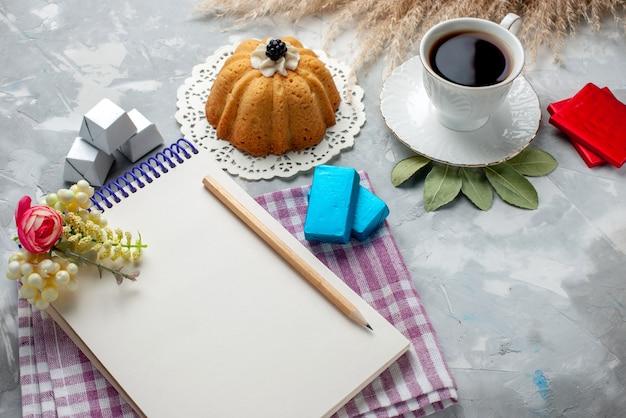 Tazza di tè caldo all'interno della tazza bianca con cioccolatini blocco note torta sulla scrivania leggera, caramelle al cioccolato tè dolce Foto Gratuite