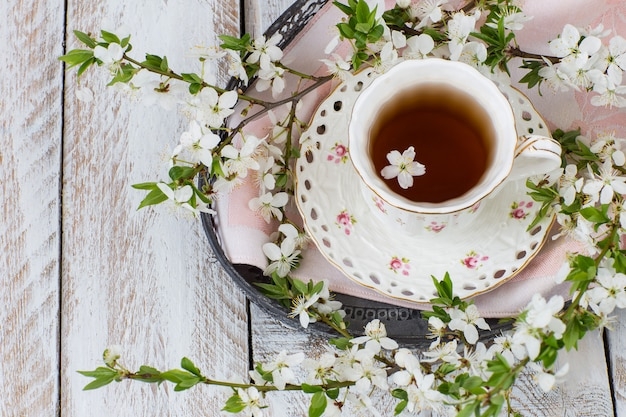 Cup of tea, napkin and blossoming cherry branches Premium Photo