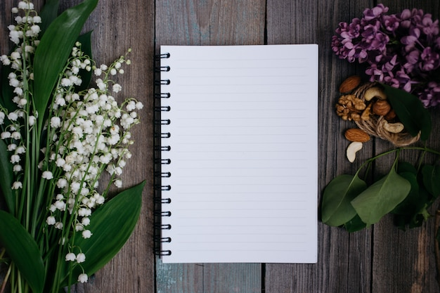 A cup of tea, nuts, lilacs and a notebook on a wooden background Premium Photo