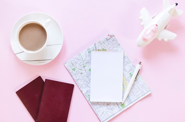 Cup of tea; passport; map; paper; pen and airplane on pink backdrop Free Photo