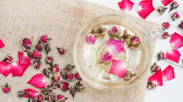 A cup of tea pink rose on a white wooden table. Premium Photo