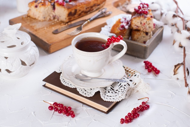 Cup of tea and saucer, cupcake with red currant on wooden board and white background, cotton flowers Premium Photo