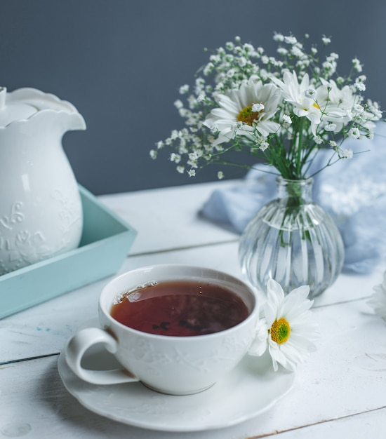 A cup of tea and white daisies on a white table. Free Photo