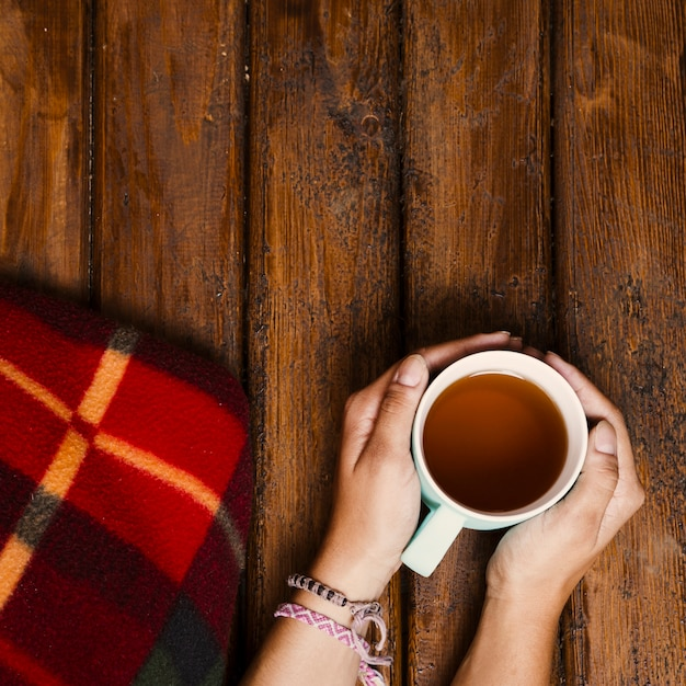 Cup of tea and winter blanket on old wood Free Photo