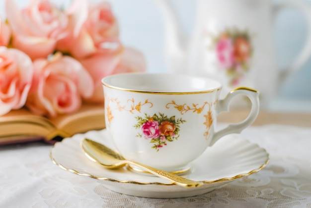 Cup of tea with book, teapot and rose flowers on blue Premium Photo