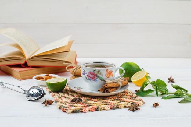 Tazza di tè con cannella e limone sulla tovaglietta quadrata con lime, una ciotola di mandorle, un colino da tè e libri sulla superficie bianca Foto Gratuite