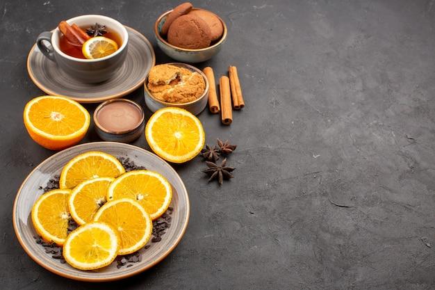 Tazza di tè con biscotti e arance fresche a fette su oscurità Foto Gratuite