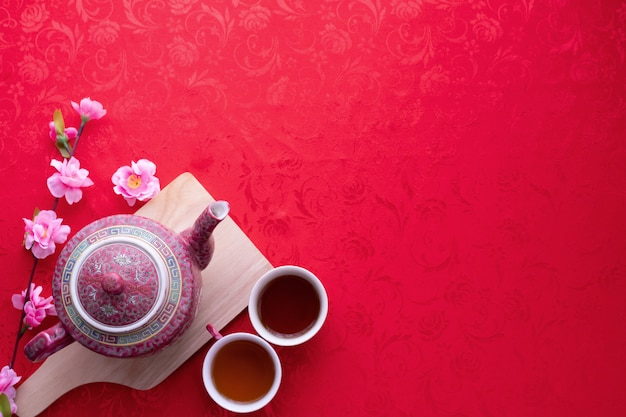 Cup of tea with copy space for text on red texture background, chinese new year background. Premium Photo