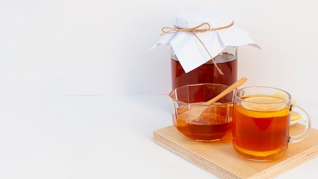 Cup of tea with lemon and a jar on a wooden board Free Photo