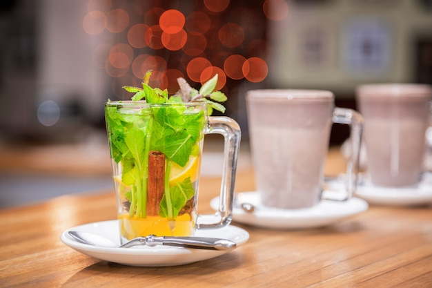 Cup of tea with mint, cinnamon and lemon of white plate Premium Photo