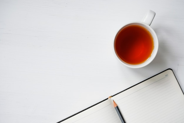 Cup of tea with notebook and pencil on white wooden table. Premium Photo