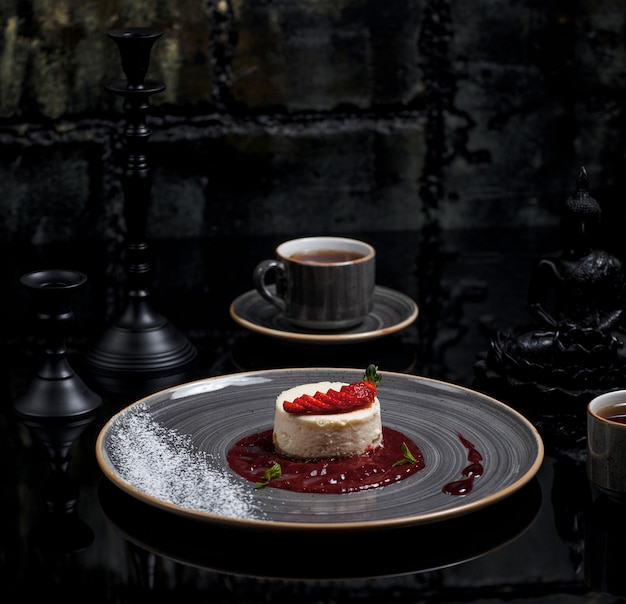 A cup of tea with ny cheesecake with berry sauce Free Photo