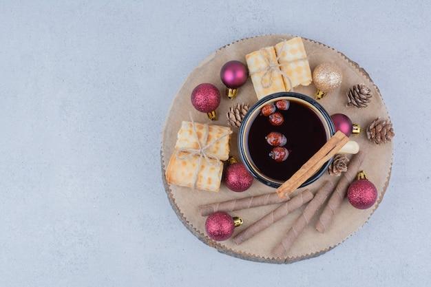 Tazza di tè con cinorrodi, biscotti e palline su tavola di legno. Foto Gratuite