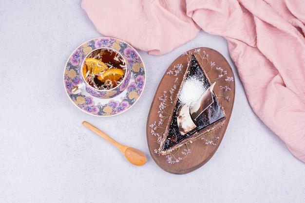 Una tazza di tè con una fetta di torta al cioccolato sulla superficie grigia Foto Gratuite