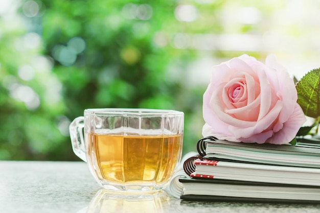 Cup of tea with spiral notebooks and sweet pink rose flower Premium Photo