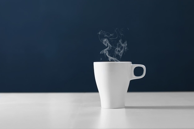 Cup of tea with steam. hot tea in a white circle. cups of hot coffee on blue background Premium Photo