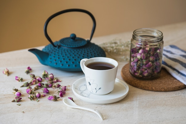 Cup of tea with teapot and breakfast elements Free Photo