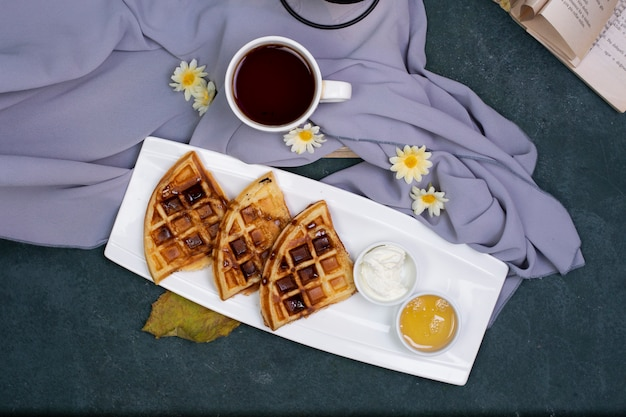 A cup of tea with waffles in the white plate. Free Photo