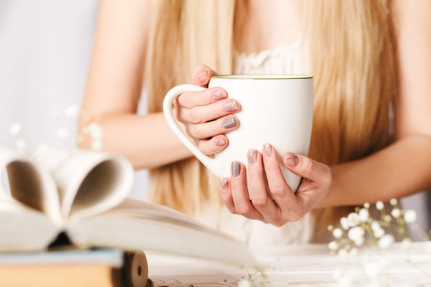 A cup of tea in women's hands. concept for spring morning. flower tea in a white cup on the table with books and flowers Premium Photo