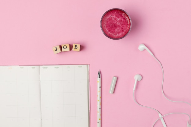 Cup of trendy superfood pink beetroot latte, pen, notepad Premium Photo
