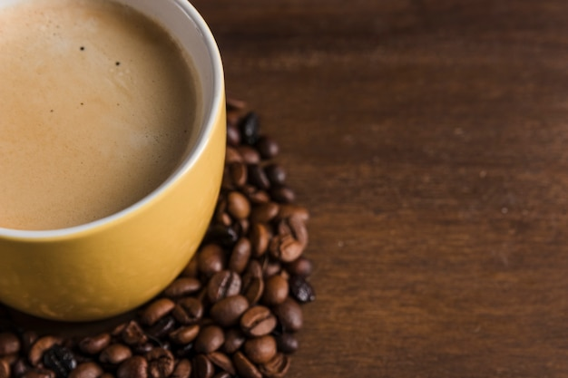 Cup with beverage and coffee beans Free Photo