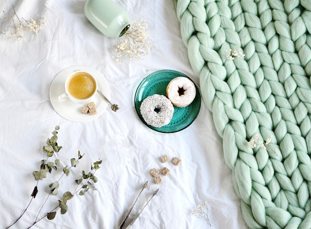 Cup with cappuccino doughnuts green pastel giant plaid bedroom morning Premium Photo