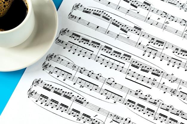 Чашка с кофе на белом блюдце и лист с нотами на синем Premium Фотографии
