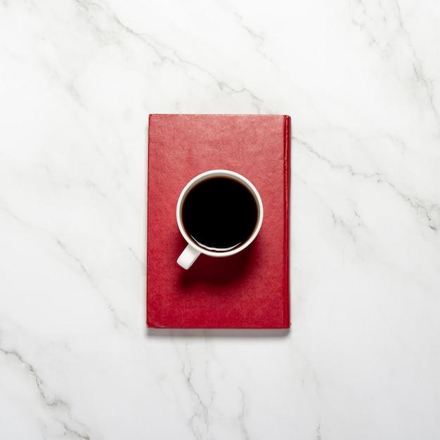 Чашка с кофе или чаем и красная книга на мраморном столе. концепция завтрака, образования, знаний, чтения книг. плоская планировка, вид сверху Premium Фотографии