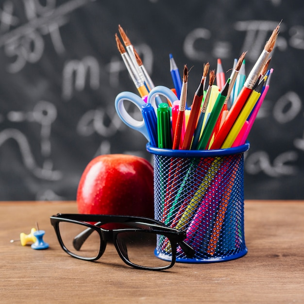 Cup with colourful stationery near glasses and apple on table Free Photo