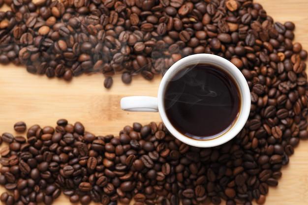 コーヒー豆に囲まれたホットコーヒーのカップ Premium写真