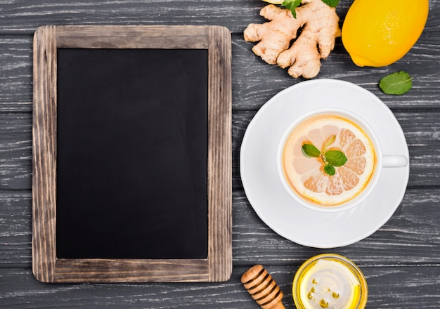 Cup with lemon tea and honey and chalkboard Free Photo