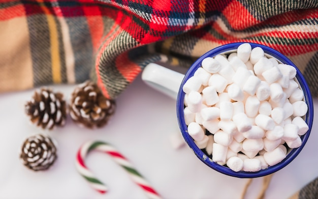 Cup with marshmallow near candy cane and snags Free Photo