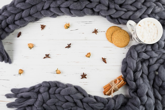 Cup with marshmallows near biscuits and scarf Free Photo