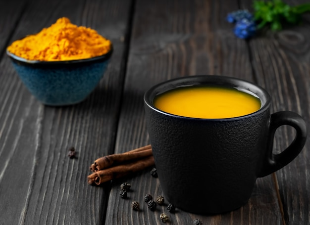 Cup with natural healthy herbal tea made from turmeric, honey and spices Free Photo