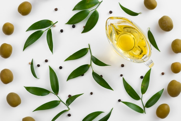 Cup with olive oil surrounded by leaves and olives Free Photo