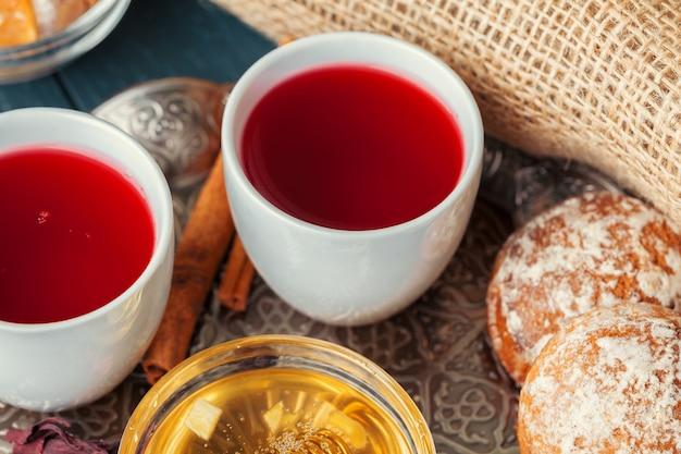 Cupれたてのフルーツとハーブティーのカップ、ダークムード。 Premium写真