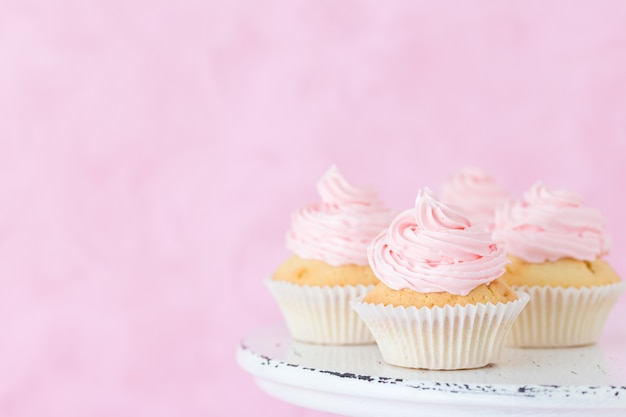 Cupcake decorated with pink buttercream on shabby shic stand on pastel pink background. Premium Photo