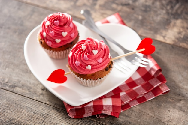 Cupcake decorated with sugar hearts and a cupid arrow for valentine's day on wooden table Premium Photo