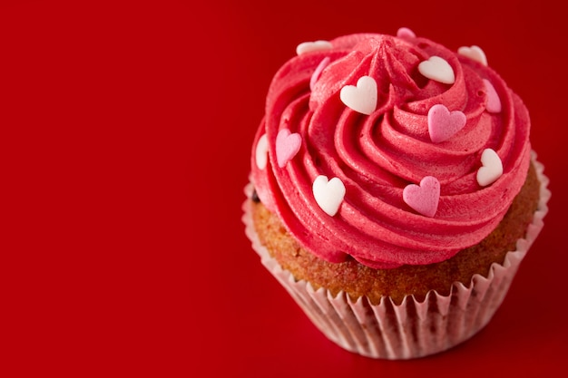Cupcake decorated with sugar hearts for valentine's day on red background Premium Photo