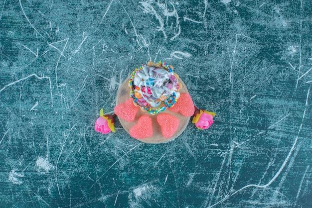 Un cupcake, marmellate e corolle di fiori impacchettati insieme su sfondo blu. foto di alta qualità Foto Gratuite